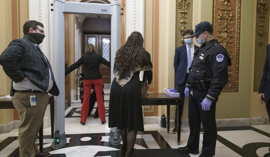 Congressional staff passes through a metal detector and security screening as they enter the House chamber, new measures put into place after a mob loyal to President Donald Trump stormed the Capitol, in Washington, Tuesday, Jan. 12, 2021. Democrats are set to pass a resolution calling on Vice President Mike Pence to invoke constitutional authority under the 25th Amendment to oust Trump. (AP Photo/J. Scott Applewhite) **FILE**