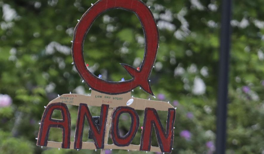 In this May 14, 2020, file photo, a person carries a sign supporting QAnon during a protest rally in Olympia, Wash, USA. (AP Photo/Ted S. Warren, File)