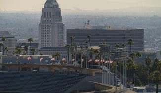 Flags fly half-mast at Dodgers Stadium in honor of the recent passing of the Hall of Fame manager Tommy Lasorda overlooking Los Angeles City Hall Monday, Jan. 11, 2021. Dodger Stadium, the home stadium of Major League Baseball's Los Angeles Dodgers holds 56,000 spectators. The The coronavirus death toll in California reached 30,000 on Monday, another staggering milestone as the nation's most populous state endures the worst surge of the nearly yearlong pandemic. (AP Photo/Damian Dovarganes)