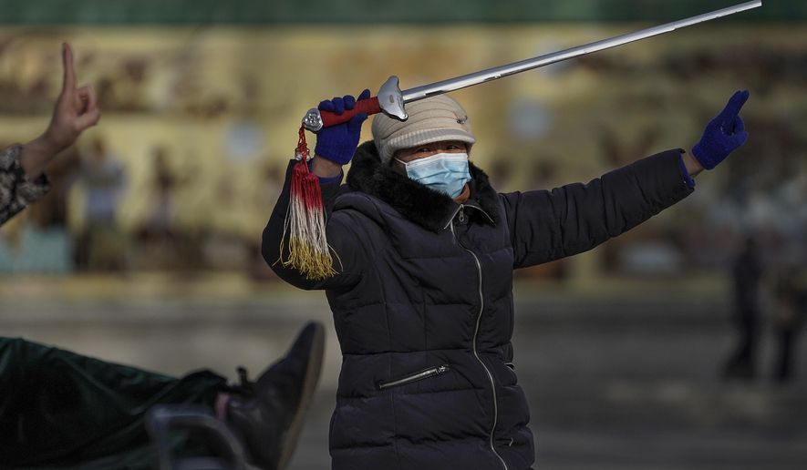A woman wearing a face mask to help curb the spread of the coronavirus performs a morning exercise with a sword at a public park in Beijing, Tuesday, Jan. 12, 2021. Lockdowns have been expanded and a major political conference postponed in a province next to Beijing that is the scene of China's most serious recent COVID-19 outbreak. (AP Photo/Andy Wong)