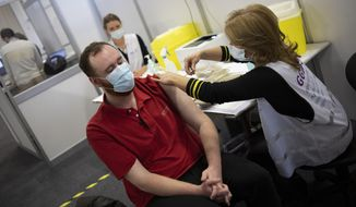 An employee of the Municipal Health Service GGD, right, administers a Pfizer-BioNTech COVID-19 vaccine to a health care worker at a coronavirus vaccination facility in Houten, central Netherlands, Friday, Jan. 8, 2021. (AP Photo/Peter Dejong)