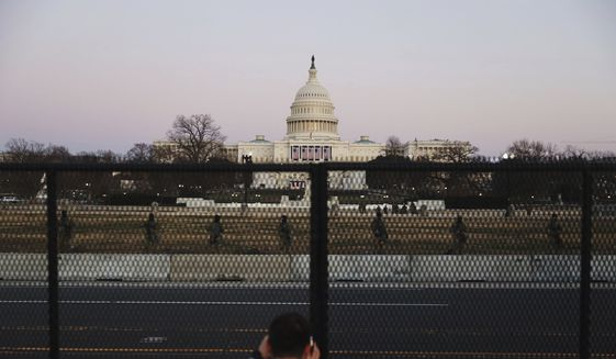 A person takes a view of the U.S. Capitol Wednesday, Jan. 13, 2021, from behind a security fence that was erected to reinforce security at the Capitol in Washington. (AP Photo/Shafkat Anowar)