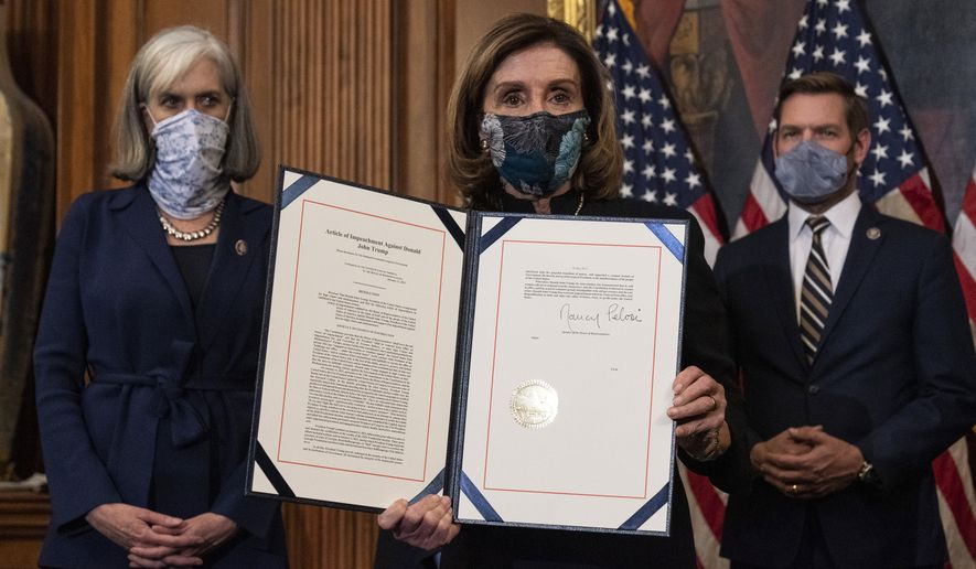 House Speaker Nancy Pelosi of Calif., holds the article of impeachment against President Donald Trump after signing it, in an engrossment ceremony before transmission to the Senate for trial on Capitol Hill, in Washington, Wednesday, Jan. 13, 2021. (AP Photo/Alex Brandon)