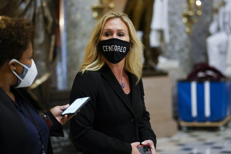 Rep. Marjorie Taylor Greene, R-Ga., walks on Capitol Hill in Washington, Wednesday, Jan. 13, 2021. (AP Photo/Susan Walsh)