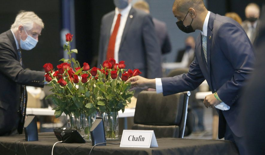 Members of the Senate, including Sen. John Edwards, D-Roanoke, left, Sen. David Suetterlein, R-Roanoke, center and Lt. Gov. Justin Fairfax, right, placed roses on the desk of the late Sen. Ben Chafin, R-Russell, on opening day of the General Assembly inside the Science Museum in Richmond, Va., Wednesday, Jan. 13, 2021. Chafin died on Jan. 1 due to complications related to the coronavirus. (Bob Brown/Richmond Times-Dispatch via AP)
