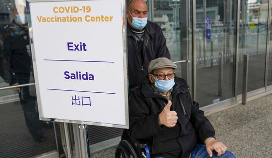 A senior citizen gives the thumbs up as he leaves a New York State COVID-19 vaccination site at the Jacob K. Javits Convention Center after receiving his first dose, Wednesday, Jan. 13, 2021, in New York. New York state expanded COVID-19 vaccine distribution Tuesday to people 65 and over, increasing access to an already short supply of doses being distributed. (AP Photo/Mary Altaffer)
