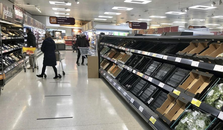 """Depleted shelves are seen in a Sainsbury's supermarker at the Forestside shopping centre in Belfast, Monday, Jan. 11, 2021. The U.K.'s biggest supermarket chains warned Wednesday, Jan. 13 that food supplies in Northern Ireland face disruption because of new checks imposed by Britain's departure from the European Union. After photos emerged showing empty shelves, the chief executives of Tesco, Sainsbury's, Asda, Iceland, Co-Op and Marks & Spencer wrote to the government saying there would be """"significant disruption"""" unless urgent action was taken to fix an """"unworkable"""" system. (David Young/PA via AP)"""