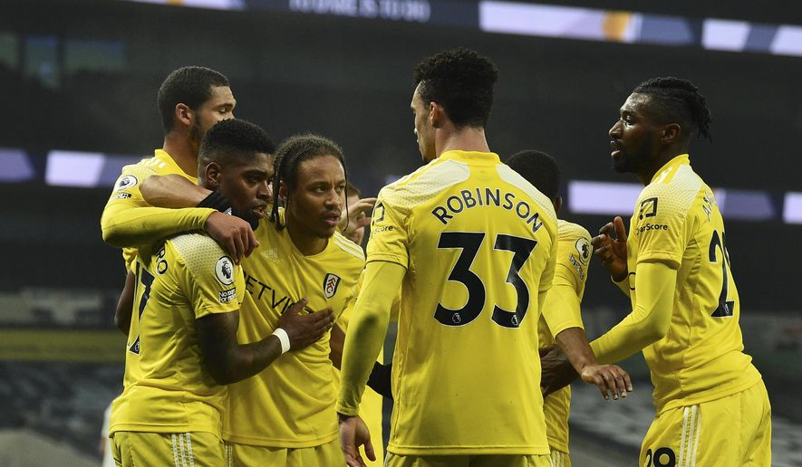 Fulham's Ivan Cavaleiro celebrates with teammates after scoring his side's opening goal during the English Premier League soccer match between Tottenham Hotspur and Fulham at the Tottenham Hotspur Stadium in London, Wednesday, Jan. 13, 2021. (Glyn Kirk/Pool via AP)