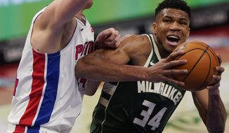 Milwaukee Bucks forward Giannis Antetokounmpo (34) is defended by Detroit Pistons center Mason Plumlee during the first half of an NBA basketball game, Wednesday, Jan. 13, 2021, in Detroit. (AP Photo/Carlos Osorio)