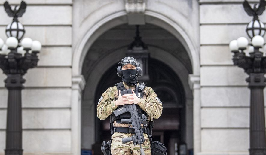 A member of the Pennsylvania Capitol Police guards the entrance to the Pennsylvania Capitol Complex in Harrisburg, Pa. Wednesday, Jan. 13, 2021. State capitols across the country are under heightened security after the siege of the U.S. Capitol last week.  (Jose F. Moreno/The Philadelphia Inquirer via AP)