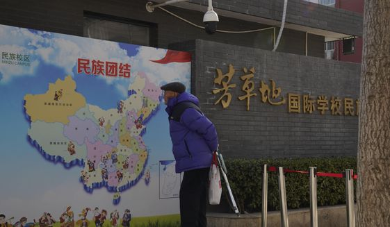 """An elderly Chinese man looks at map of Chinese showing its different ethnic groups and the slogan """"Ethnic Unity"""" in Beijing, China Monday, Jan. 11, 2021. A Chinese official on Monday denied Beijing has imposed coercive birth control measures among Muslim minority women, following an outcry over a tweet by the Chinese Embassy in Washington claiming that government polices had freed women of the Uighur ethnic group from being """"baby-making machines."""" (AP Photo/Ng Han Guan)"""