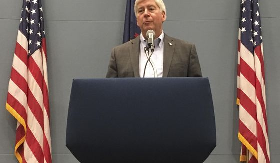 FILE - In this Tuesday, Sept. 25, 2018, file photo, then-Michigan Gov. Rick Snyder speaks with reporters during a news conference at his office in Lansing, Mich. Former Michigan Gov. Rick Snyder has been charged with two counts of willful neglect of duty in the Flint water crisis. (AP Photo/David Eggert, File)