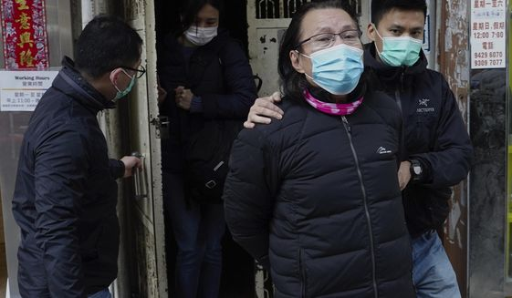 District councillor and lawyer Daniel Wong Kwok-tung, center, is escorted by police outside his office after police search in Hong Kong, Thursday, Jan. 14, 2021. Wong, a member of the city's Democratic Party, is known for providing legal assistance to hundreds of protesters arrested during the anti-government protests in Hong Kong in 2019.  Hong Kong national security police on Thursday arrested a lawyer and 10 others on suspicion of helping 12 Hong Kongers try to flee the city, local media reported in the latest arrests in an ongoing crackdown on dissent. (AP Photo/Vincent Yu)