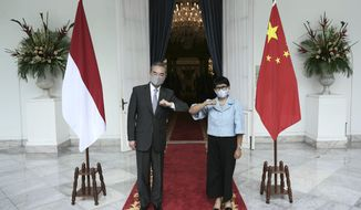 In this photo released by Indonesian Foreign Ministry, Chinese Foreign Minister Wang Yi, left, poses for photographers with his Indonesian counterpart Retno Marsudi during their meeting in Jakarta, Indonesia, Wednesday, Jan. 13, 2021. Wang pledged that China will help Indonesia defeat the coronavirus, including providing vaccines and the strengthen economic cooperation with Indonesia in addition to strengthening cooperation in the health sector in overcoming the COVID-19 pandemic. (Indonesian Foreign Ministry via AP)