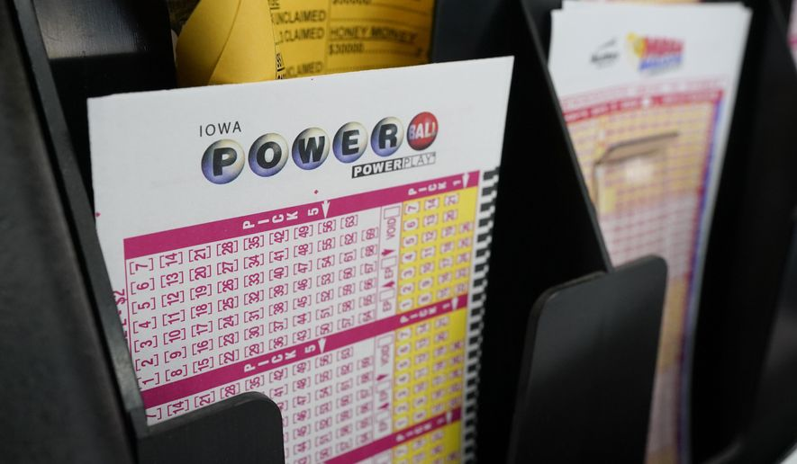 Blank forms for the Powerball lottery sit in a bin at a local grocery store, Tuesday, Jan. 12, 2021, in Des Moines, Iowa. Lottery players have a chance to win the largest jackpots in nearly two years as Tuesday's Mega Millions has grown to an estimated $625 million and Wednesday's Powerball to an estimated $550 million. (AP Photo/Charlie Neibergall)