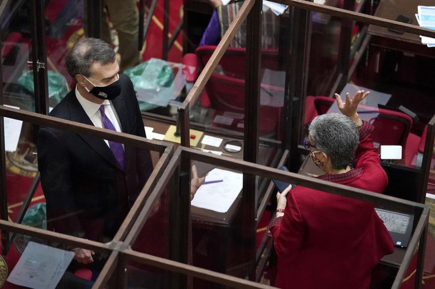 Maryland Sen. Cheryl Kagan, right, D-Montgomery County, and Sen. Brian Feldman, D-Montgomery County, are separated by plexiglass barriers while talking before the start of the state's 2021 legislative session, Wednesday, Jan. 13, 2021, in Annapolis, Md. (AP Photo/Julio Cortez)
