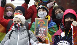 Human rights activists show an altered image with colors symbolizing LGBT rights as they gathered outside the provincial court in Plock, Poland, Wednesday, Jan. 13, 2021. Three activists went on trial Wednesday at the court on charges of having offending religious sentiment by adding the LGBT rainbow symbol to posters of the revered icon, The Black Madonna and Baby Jesus, and publicly displaying the altered image on garbage bins and mobile toilets. (AP Photo/Czarek Sokolowski)