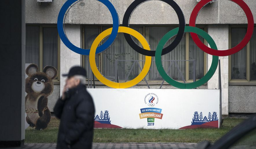 """FILE - In this Nov. 28, 2019 file photo Olympic Rings and a model of Misha the Bear Cub, the mascot of the Moscow 1980 Olympic Games, left, are seen in the yard of Russian Olympic Committee building in Moscow, Russia. In the report detailing its decision to shorten Russia's ban from the Olympics, the highest court in sports blasted that country's leaders for engaging in """"a cover up of the cover-up"""" in a desperate attempt to deny their culpability, but reduced the punishment nonetheless, Wednesday, Jan. 13, 2021. (AP Photo/Pavel Golovkin, file)"""