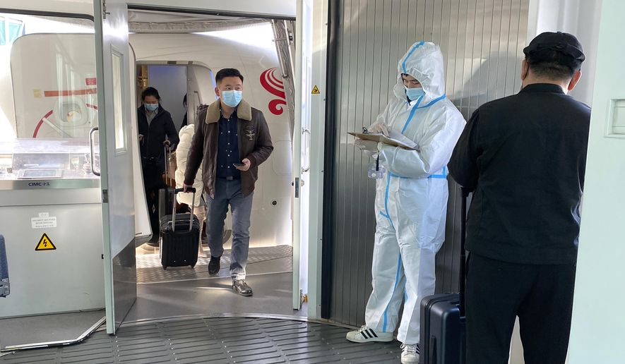 Passengers wearing face masks to protect against the spread of the coronavirus exit a plane after arriving at Wuhan Tianhe International Airport in Wuhan in central China's Hubei Province, Thursday, Jan. 14, 2021. China is seeing a new surge in coronavirus cases in its frozen northeast as a World Health Organization team was due to arrive to probe the origins of the pandemic. (AP Photo/Ng Han Guan)