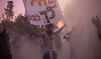 """An Israeli anti-government protester holds a banner as he is enveloped in the smoke from a bonfire outside of the official residence of Prime Minister Benjamin Netanyahu on the day his corruption trial was originally scheduled before it was postponed, in Jerusalem, Wednesday, Jan. 13, 2021. In Hebrew, the sign reads: """"Coward! Go to trial!"""" (AP Photo/Maya Alleruzzo)"""