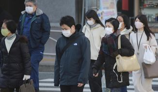 People wearing face masks to protect against the spread of the coronavirus cross an intersection on a street in Tokyo, Wednesday, Jan. 13, 2021. (AP Photo/Koji Sasahara)