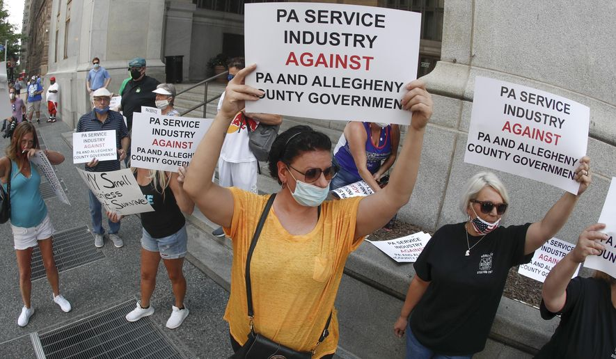 Service Industry workers and supporters hold protest signs in front of Allegheny County offices in Pittsburgh. (AP Photo/Keith Srakocic, File)