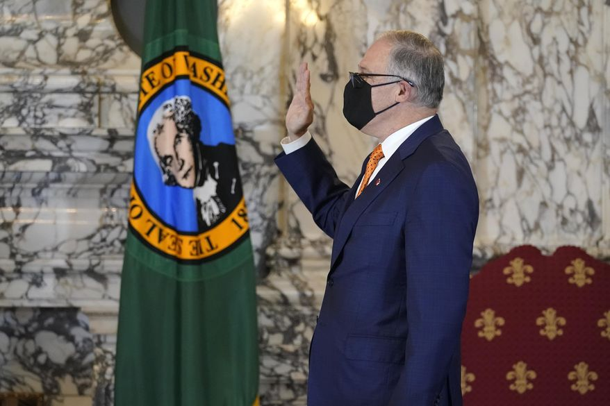 Washington Gov. Jay Inslee takes the oath of office for his third term as Governor, Wednesday, Jan. 13, 2021, during a ceremony at the Capitol in Olympia, Wash. (AP Photo/Ted S. Warren)