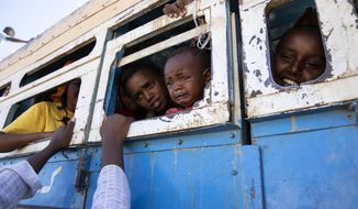 Refugees who fled the conflict in Ethiopia's Tigray region ride a bus going to the Village 8 temporary shelter, near the Sudan-Ethiopia border, in Hamdayet, eastern Sudan, on Dec. 1, 2020. (AP Photo/Nariman El-Mofty)