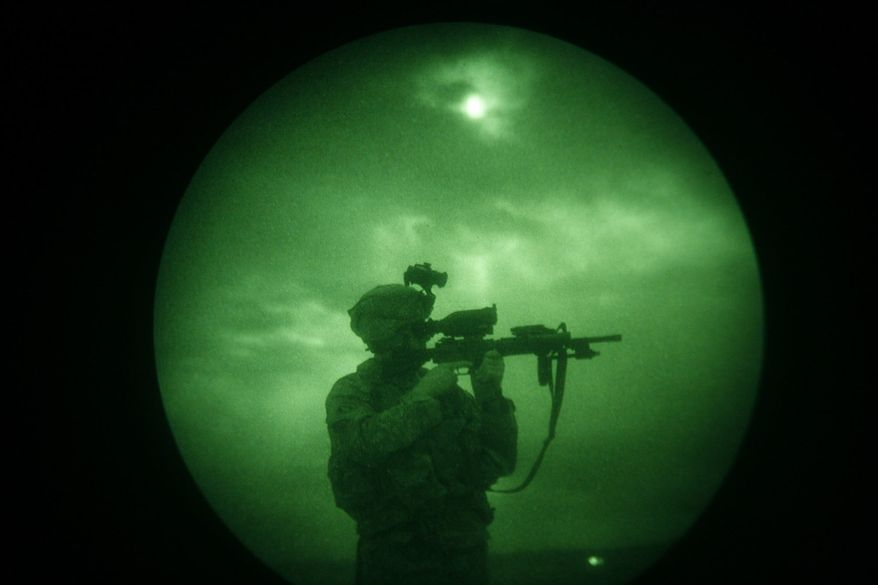 In this Monday, April 21, 2008 file photo, a U.S soldier looks through the scope of his weapon during a night patrol in Mandozai, in Khost province, Afghanistan, seen through night vision equipment. About 400,000 veterans had a PTSD diagnosis in 2013, according to the Veterans Affairs health system. (AP Photo/Rafiq Maqbool)
