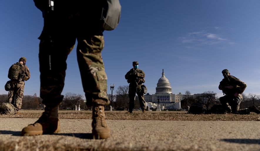 Armed members of the National Guard stand guard outside the Capitol Building on Capitol Hill in Washington, Thursday, Jan. 14, 2021. (AP Photo/Andrew Harnik)