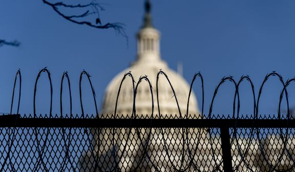 The dome of the U.S. Capitol building is visible through razor wire installed on top of fencing on Capitol Hill in Washington, Thursday, Jan. 14, 2021. (AP Photo/Andrew Harnik)