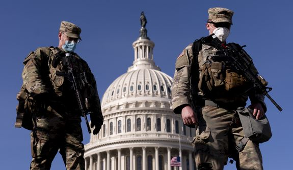 Members of the National Guard walk past the Dome of the Capitol Building on Capitol Hill in Washington, Thursday, Jan. 14, 2021. (AP Photo/Andrew Harnik)