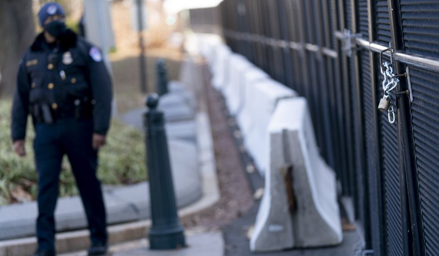 A U.S. Capitol Police officer walks along fencing installed along the perimeter of the Capitol building on Capitol Hill in Washington, Thursday, Jan. 14, 2021. (AP Photo/Andrew Harnik)