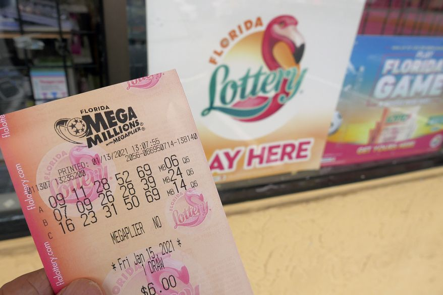In this Wednesday, Jan. 13, 2021, file photo, a customer shows off a Mega Millions lottery ticket after purchasing it, in Orlando, Fla. The nations two national lottery games are designed to produce immense jackpots that generate huge sales, and the recipe certainly is working now as prizes on Thursday reached a combined $1.39 billion. The next drawing for Mega Millions is Friday night, when a $750 million prize will be up for grabs. (AP Photo/John Raoux, File)