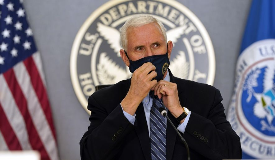 Vice President Mike Pence adjusts his face mask as he listens during a briefing about the upcoming presidential inauguration of President-elect Joe Biden and Vice President-elect Kamala Harris, at FEMA headquarters, Thursday, Jan. 14, 2021, in Washington. (AP Photo/Alex Brandon, Pool)