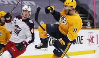 Nashville Predators center Luke Kunin (11) celebrates after scoring a goal against the Columbus Blue Jackets in the second period of an NHL hockey game Thursday, Jan. 14, 2021, in Nashville, Tenn. At left is Blue Jackets defenseman Dean Kukan (46). (AP Photo/Mark Humphrey)