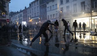 Rioters throw stones in the Belgium capital, Brussels, Wednesday, Jan. 13, 2021, at the end of a protest asking for authorities to shed light on the circumstances surrounding the death of a 23-year-old Black man who was detained by police last week in Brussels. The demonstration in downtown Brussels was largely peaceful but was marred by incidents sparked by rioters who threw projectiles at police forces and set fires before it was dispersed. (AP Photo/Francisco Seco)