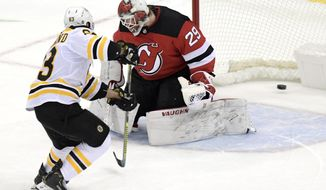Boston Bruins center Brad Marchand (63) scores a goal past New Jersey Devils goaltender Makenzie Blackwood (29) during the shootout of an NHL hockey game Thursday, Jan. 14, 2021, in Newark, N.J. (AP Photo/Bill Kostroun)