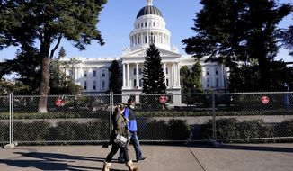 A temporary six-foot high chain link fence surrounds the state Capitol because of concerns over the potential for civil unrest, in Sacramento, Calif., Thursday, Jan. 14, 2021. Along with the fence, Gov. Gavin Newsom has mobilized he National Guard and other precautions over concerns that protests around next week's inauguration of President-elect Joe Biden could turn violent and destructive. (AP Photo/Rich Pedroncelli)