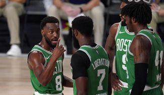 Boston Celtics' Kemba Walker (8) talks to Jaylen Brown (7), Robert Williams III (44) and Brad Wanamaker, right rear, on the floor during the first half of Game 4 of an NBA basketball Eastern Conference final against the Miami Heat on Wednesday, Sept. 23, 2020, in Lake Buena Vista, Fla. (AP Photo/Mark J. Terrill)