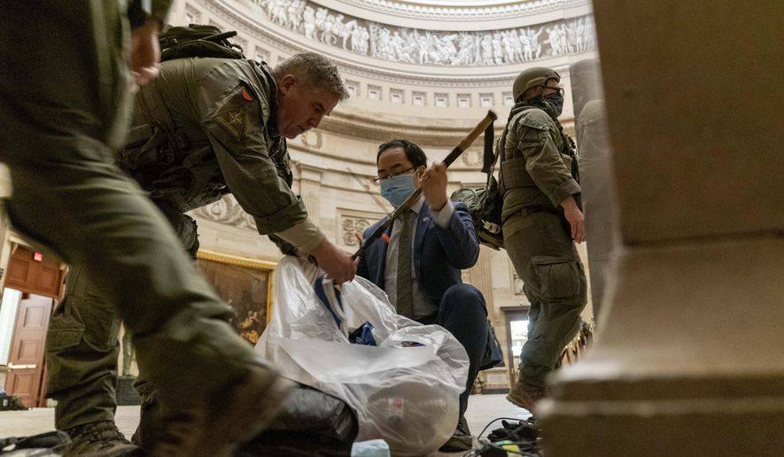 Rep. Andy Kim, D-N.J., helps ATF police officers clean up debris and personal belongings strewn across the floor of the Rotunda in the early morning hours of Thursday, Jan. 7, 2021, after protesters stormed the Capitol in Washington, on Wednesday. (AP Photo/Andrew Harnik)