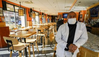 In this file photo, Andrew Walcott, owners of Fusion East Caribbean & Soul Food restaurant, poses for a photo at the restaurant in East New York neighborhood of the Brooklyn borough of New York, Thursday, Jan. 7, 2021. Walcott had to furlough four employees at his restaurant just before Christmas, after New York state stopped allowing indoor dining. (AP Photo/Mary Altaffer) **FILE**