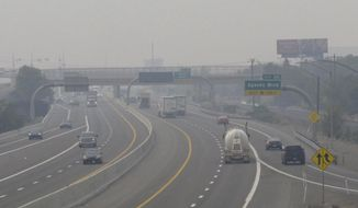 """FILE - In this Wednesday, Aug. 19, 2020. file photo, smoke from California wildfires up to 200 miles away obscures the view of traffic traveling on Interstate 80, looking west in Sparks, Nev. Local schools canceled all outdoor activities as the air quality index approached the """"very unhealthy"""" category for the general population Wednesday afternoon. (AP Photo/Scott Sonner)"""