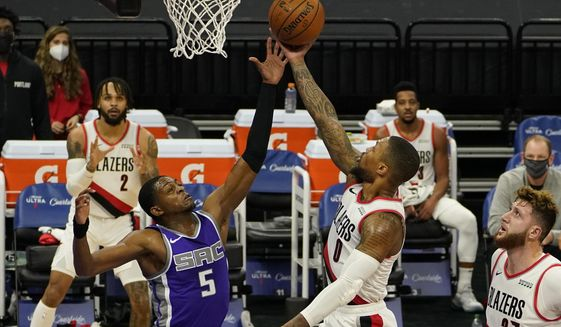 Portland Trail Blazers guard Damian Lillard, right, goes to the basket against Sacramento Kings guard De'Aaron Fox, left, during the first quarter of an NBA basketball game in Sacramento, Calif., Wednesday, Jan. 13, 2021. (AP Photo/Rich Pedroncelli)