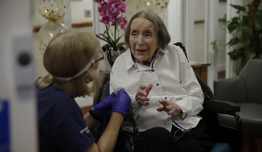 Care home resident Joan Potts, aged 102, is seen through a viewing screen installed for residents to safely receive visits from family members, as she speaks to Dr. Jane Allen before receiving her first dose of the Oxford/AstraZeneca COVID-19 vaccine at the Wimbledon Beaumont Care Home, run by Barchester, in south west London, Wednesday, Jan. 13, 2021, during England's third national lockdown since the coronavirus outbreak began. (AP Photo/Matt Dunham)
