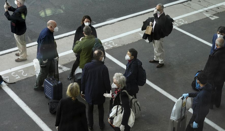 Members of the World Health Organization (WHO) team gather after arriving at the airport in Wuhan in central China's Hubei province on Thursday, Jan. 14, 2021. A global team of researchers arrived Thursday in the Chinese city where the coronavirus pandemic was first detected to conduct a politically sensitive investigation into its origins amid uncertainty about whether Beijing might try to prevent embarrassing discoveries. (AP Photo/Ng Han Guan)