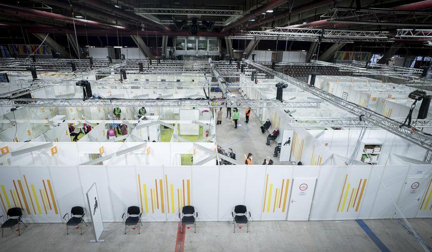 People stay in the new open Erika-Hess-Eisstadion vaccine center in Berlin, Germany, Thursday, Jan. 14, 2021. (Kay Nietfeld/Pool via AP)