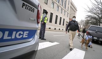 Capitol Police K9 Officer David Chaulkin and Gunner leave the Virginia State Supreme Court building in Richmond, Va., after checking for a suspected bomb, Thursday, Jan. 15, 2021. They found no explosive devices.  (Bob Brown/Richmond Times-Dispatch via AP) **FILE**