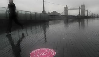 A jogger exercises on the banks of the river Thames with the backdrop of Tower Bridge in London, Thursday, Jan. 14, 2021 during England's third national lockdown to curb the spread of coronavirus. (AP Photo/Kirsty Wigglesworth)