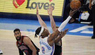 Oklahoma City Thunder guard Shai Gilgeous-Alexander (2) shoots between Chicago Bulls guard Garrett Temple (17) and forward Lauri Markkanen during overtime of an NBA basketball game Friday, Jan. 15, 2021, in Oklahoma City. (AP Photo/Sue Ogrocki)
